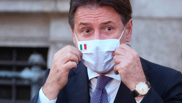 ARCHIV - Giuseppe Conte, Ministerpräsident von Italien, richtet seinen Mund-Nasen-Schutz bei einer Pressekonferenz. Foto: Mauro Scrobogna/LaPresse/AP/dpa