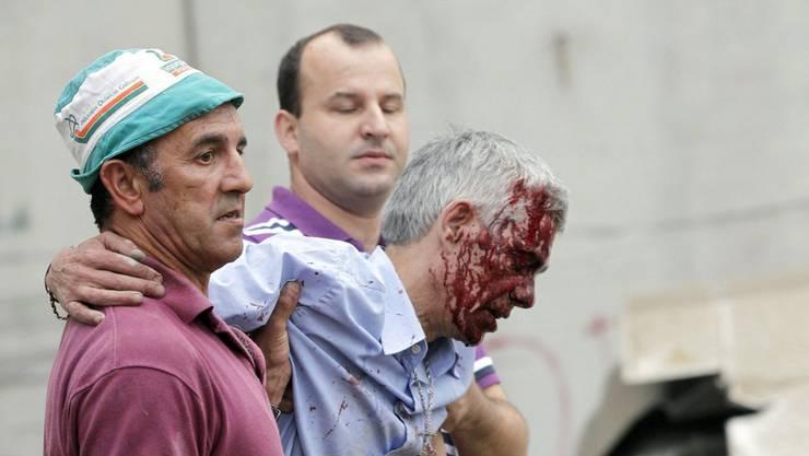 Lokführer Francisco José Garzón nach dem Unfall. Der verletzte Lokführer wird wird von zwei Männern gestützt.