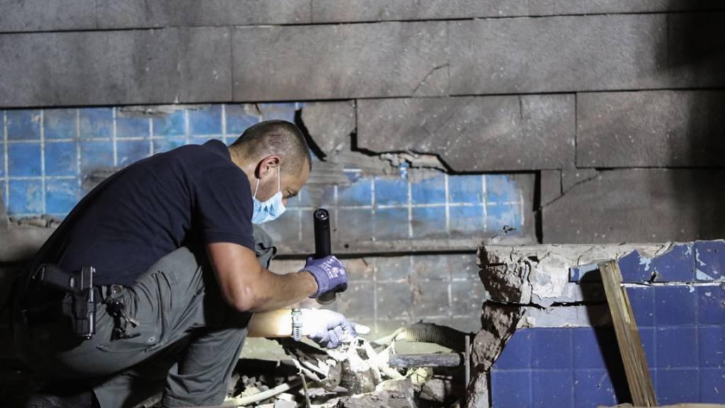 dpatopbilder - Ein Offizier untersucht Trümmer, nachdem eine Rakete aus dem Gazastreifen auf Israel abgefeuert wurde. Foto: Ilia Yefimovich/dpa