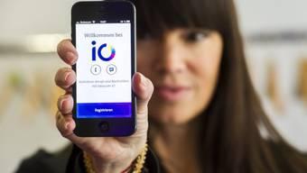 Eine Frau präsentiert ein iPhone mit der neuen Swisscom iO App
