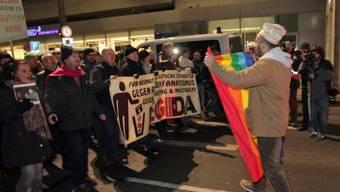 Mann mit Friedensfahne tritt in Leipzig dem Legida-Marsch entgegen