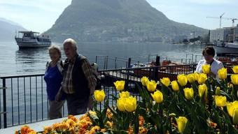 Leute spazieren am Quai von Lugano - im Hintergrund der Monte Salvatore (Archiv)