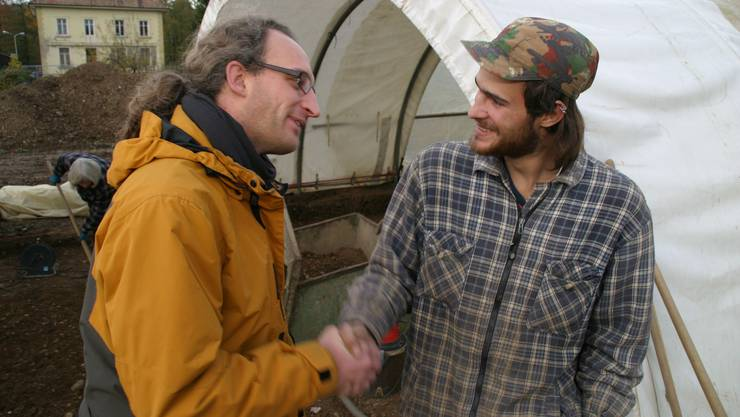 Gratulation: Finder Riet Grubenmann (rechts) wird von Ausgrabungsleiter Hannes Flück beglückwünscht. (Bild: Michael Spillmann)