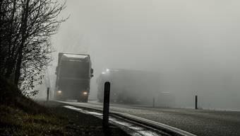 Tauchen aus dem Nebel auf: Zwei Lastwagen auf der Staffelegg-Passhöhe. (Archiv)
