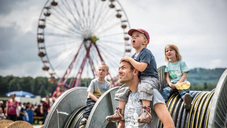 Vater und Sohn beobachten eine Attraktion am AEW-Fest. Im Hintergrund das Riesenrad.