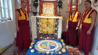 Die drei Mönche Geshe Lobsang Soepa (v.l.), Geshe Lobsang Tsondu und Geshe Jampa Gyatso mit einem kleinen Sandmandala in Brügg BE.