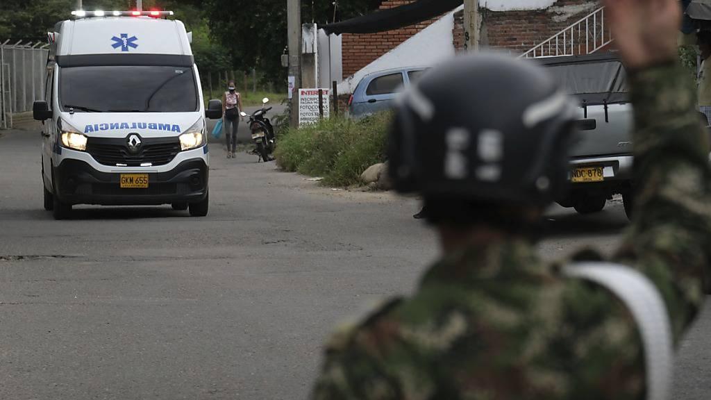 Ein Soldat gibt einem Krankenwagen Signale. Bei einem Anschlag auf einen Militärstützpunkt im Osten Kolumbiens sind dutzende Menschen verletzt worden. Foto: Ferley Ospina/AP/dpa