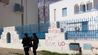 """ARCHIV - Passantinnen gehen am 17.10.2011 in Sidi Bouzid an mit Graffiti besprühten Mauern vorbei. (zu dpa """"Ein Gemüsehändler zündet sich an: 10 Jahre Aufstände in der arabischen Welt"""") Foto: picture alliance / dpa"""