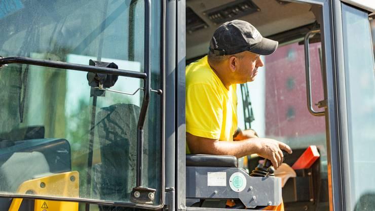 Bauarbeiter bei der Kreuzung Schönenwerd sind an den Belagsarbeiten und arbeiten mit 165 Grad heissem Asphalt in der Sommerhitze.