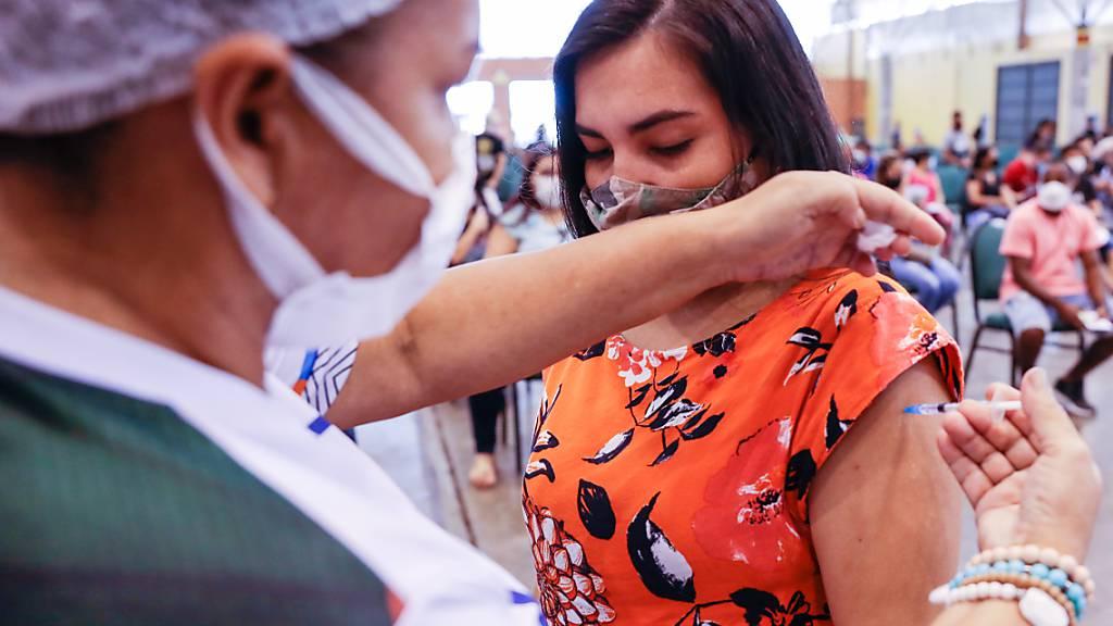 HANDOUT - Auf diesem von der Regierung von Manaus zur Verfügung gestellten Bild verabreicht eine Mitarbeiterin des Gesundheitswesens einer Frau eine Corona-Impfung im Rahmen der Impfkampagne für Menschen über 24 Jahren. Foto: Joao Viana/Secom/Prefeitura Manaus/dpa - ACHTUNG: Nur zur redaktionellen Verwendung und nur mit vollständiger Nennung des vorstehenden Credits