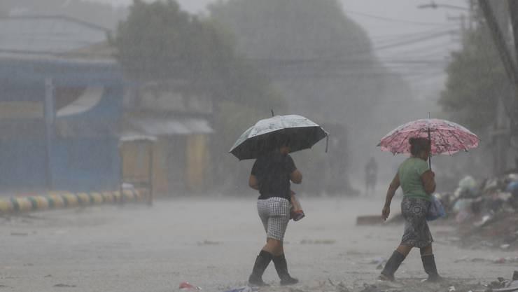 Zwei Frauen gehen bei starkem Regen über eine Straße. Rund zwei Wochen nach dem verheerenden Hurrikan «Eta» hat ein zweiter gefährlicher Sturm in Mittelamerika Land erreicht. Foto: Delmer Martinez/AP/dpa