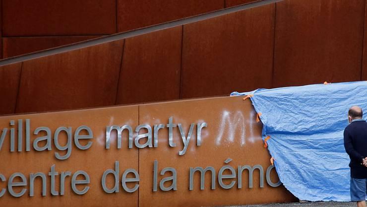 Ein Besucher betrachtet ein Graffiti auf dem Schriftzug am Eingang der Gedenkstätte in Oradour-sur-Glane. Unbekannte hatten unter anderem das Wort «Märtyrer» im Schriftzug mit weißer Farbe durchgestrichen und «Lügner» daneben geschrieben. Foto: Pascal Lachenaud/AFP/dpa