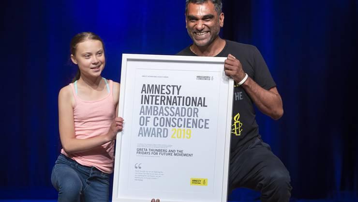 Greta Thunberg nimmt am Montag von Amnesty International Secretary General Kumi Naidoo ihren Preis als  «Ambassador of Conscience» entgegen.  (EPA/ERIK S. LESSER)