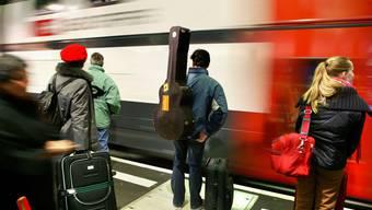 Reisende warten auf einen einfahrenden Zug.