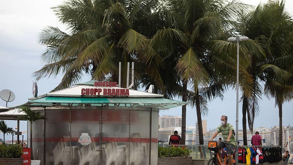 Ein Mann fährt mit dem Rad an einem geschlossenen Kiosk am brasilianischen Strand Copacabana vorbei. (Archivbild) Foto: Fernando Souza/dpa