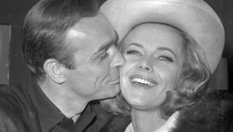 Sean Connery küsst Honor Blackman auf einer Party im März 1964 in den Pinewood Film Studios in Iver Heath, England.