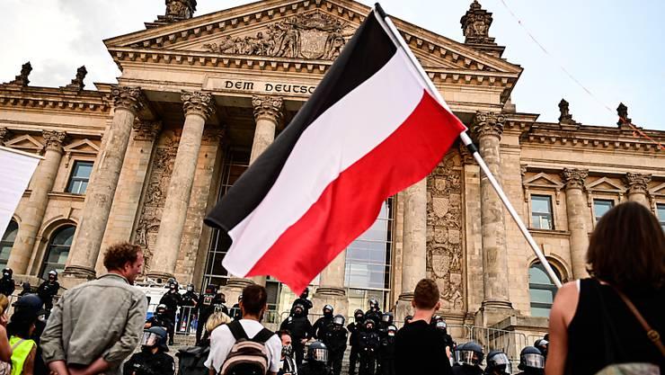 Teilnehmer einer Kundgebung gegen die Corona-Maßnahmen stehen vor dem Reichstag, ein Teilnehmer hält eine Reichsflagge. Foto: Fabian Sommer/dpa