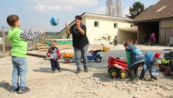 Sandra Schmid Koch spielt mit den Krippenkindern im Hof, im Hintergrund das gelbe neue Gebäude, in dessen Keller die Holzschnitzelheizung steht. Andrea Weibel