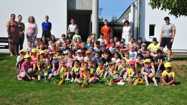 Schulanfang: Kindergarten- und Schulkinder sowie ihre Lehrkräfte lächeln für das Erinnerungsfoto.      Foto: Beat Wyttenbach
