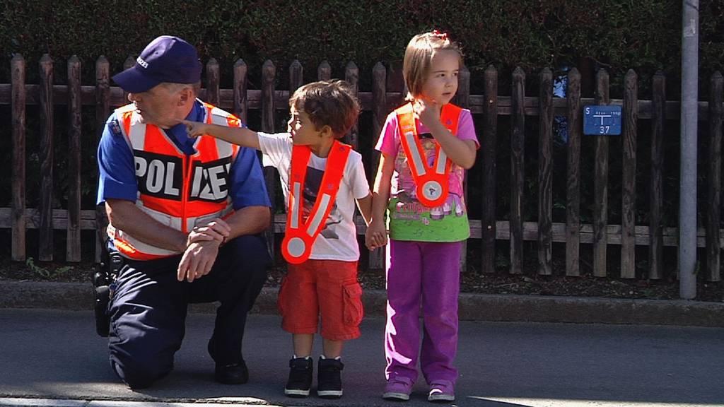 Ein Verkehrspolizist bringt den Kleinsten bei, wie sie sich auf der Strasse richtig verhalten.