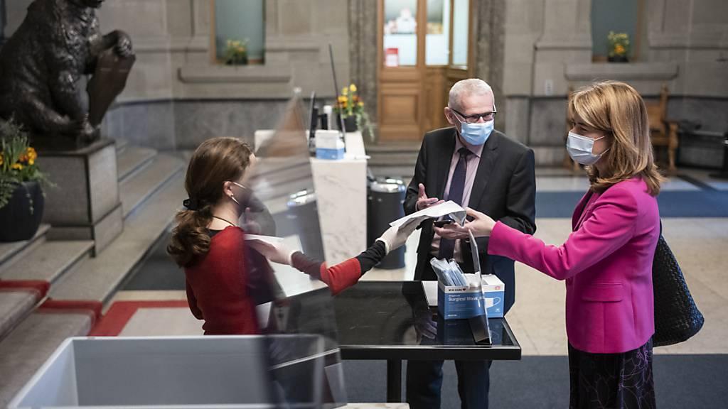 FDP-Präsidentin Petra Gössi (SZ) und Nationalrat Leo Müller (CVP/LU) geben bei einer Mitarbeiterin der Parlamentsdienste ihre Covid-19 Tests ab.
