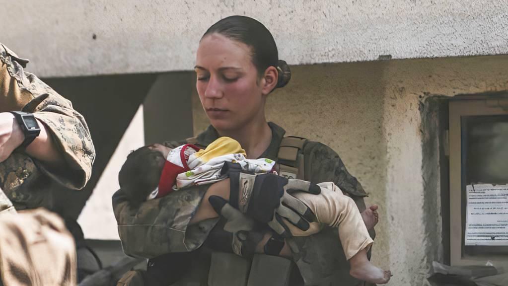 Die Unteroffizierin Nicole Gee vom US Marine Corps beruhigt ein Kleinkind am Flughafen in Kabul. Tage danach stirbt sie bei einem Terroranschag.