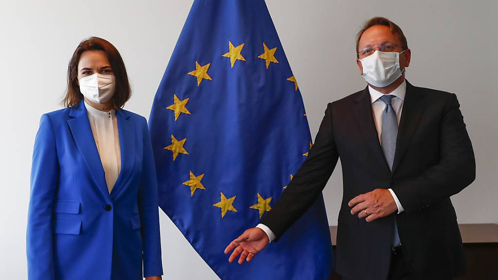 Swetlana Tichanowskaja, Oppositionsführerin aus Belarus, und Oliver Varhelyi, Erweiterungskommissar der EU, stehen zusammen vor einer Fahne der EU während eines Treffens der Außenminister der EU im Gebäude des Europäischen Rates. Foto: Johanna Geron/Pool Reuters/AP/dpa