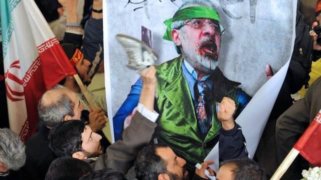 Anhänger der Regierung schlagen in Teheran ein Bild von Oppositionsführer Mussawi mit Schuhen, um ihre Verachtung auszudrücken