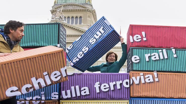 Regula Rytz, Vorstandsmitglied der Alpeninitiative und Grünen-Präsidentin stapelt mit Manuel Herrmann, Leiter Alpenschutzpolitik der Alpeninitiative, symbolisch Container.