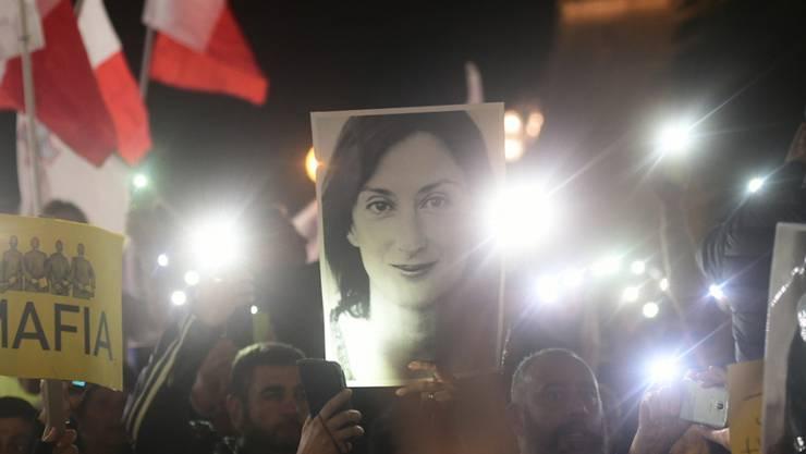 Demonstranten vor dem Büro des Ministerpräsidenten Joseph Muscat halten ein Bild der ermordeten Journalistin Daphne Caruana Galizia, die über Korruption in Malta berichtet hatte. Nun droht ein Zeuge mehrere Minister und Muscats Ex-Stabschef Keith Schembri zu belasten. (Foto: Str/AP Keystone)