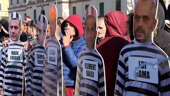 Die Demonstranten halten Pappfiguren von Ministerpräsident Edi Rama und seinen Ministern in Häftlingskleidung.
