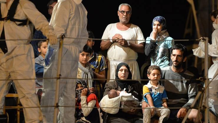 Mit Auswirkungen auf die Schweiz: In Italien kommen täglich Flüchtlinge an wie diese Familie, die die italienische Marine aus einem Schlepperschiff barg.