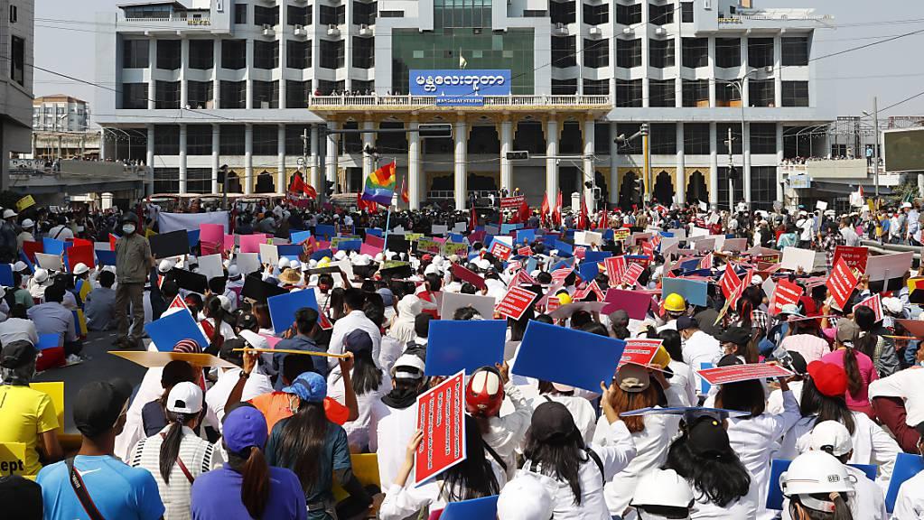 Teilnehmer eines Protestes gegen den jüngsten Militärputsch versammeln sich mit Plakaten vor dem Bahnhofsgebäude. Myanmars entmachtete Regierungschefin Suu Kyi bleibt zunächst weiter in Gewahrsam. Foto: Uncredited/AP/dpa