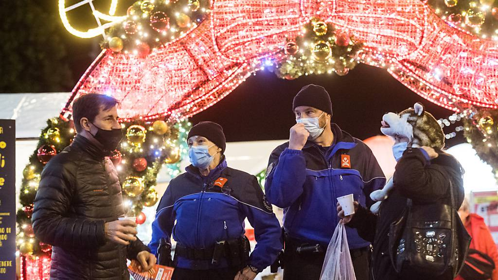 Weihnachten während Zeiten Coronas: Polizisten und Besucher auf dem Weihnachtsmarkt auf der Piazza Riforma in Lugano. (Archivbild)