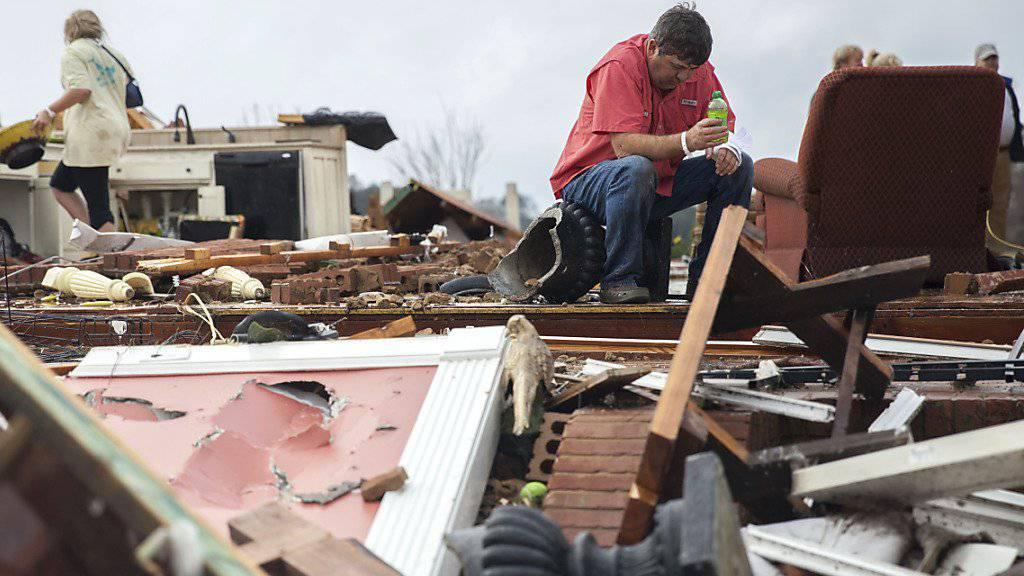Ein Mann sitzt in den Trümmern seines durch einen Tornado zerstörten Hauses.