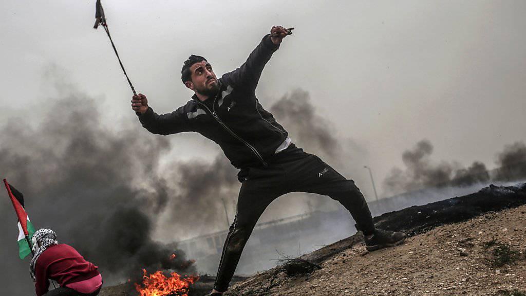 David gegen Goliath: Palästinensische Jugendliche schleudern Geschosse über den Grenzzaun des Gazastreifens gegen israelische Soldaten.
