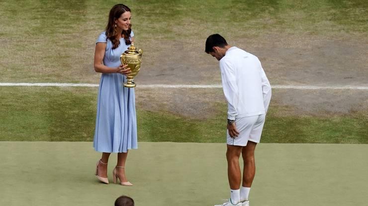 Herzogin Kate übergibt Djokovic den Pokal mit der Ananas obendrauf.