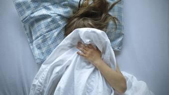 Ein kleines Mädchen liegt in einem Bett (gestellte Aufnahme)
