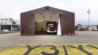 Die Feuerwehrfahrzeuge sind provisorisch in einem Zelt untergebracht.