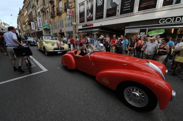 Besucher bestaunen den schönen roten Wagen