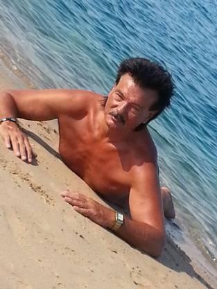 Für seine Lieblingssonnencréme Piz Buin räckelt er sich am Strand.