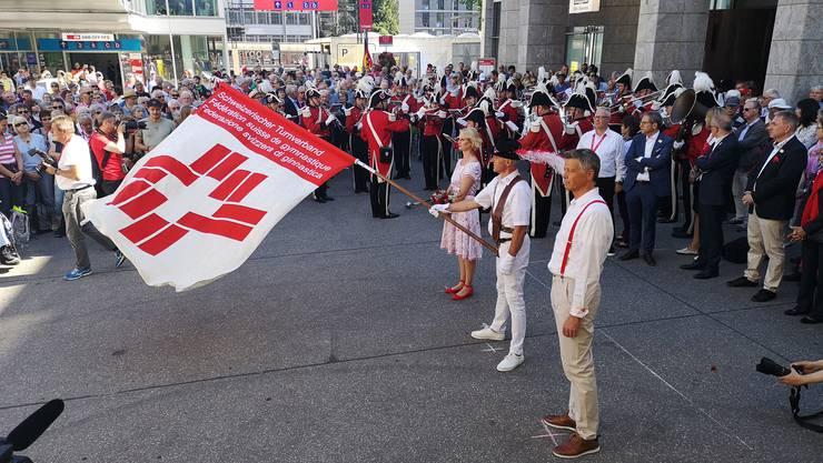 Der neue Zentralfähnrich Sepp Huwyler schwingt die Fahne vor dem Bahnhof Aarau. Neben ihm die Ehrenleute Christian Oehler und Karin Kramer.