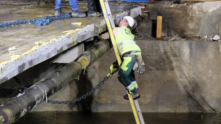 Damit der Kran die Brücke herausheben konnte, mussten Metallketten angebracht werden. Dafür stieg einer der Arbeiter auf eine Leiter, die mitten in der Reppisch stand.