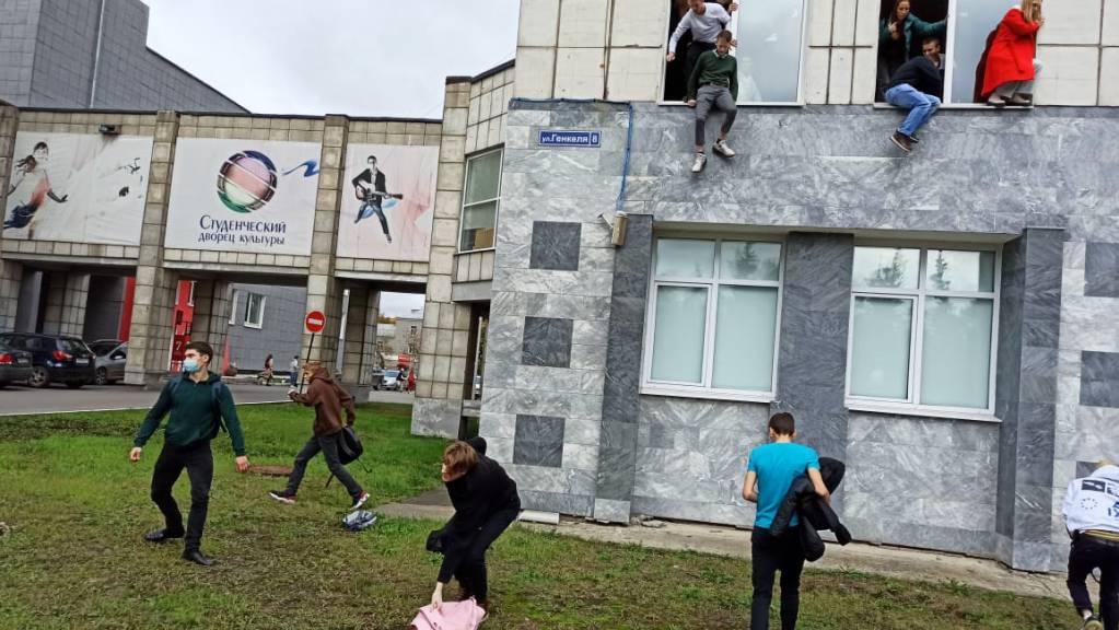 Studenten springen während einer Schießerei aus dem Fenster einer Universität. Ein Mann hat in der russischen Stadt Perm am Ural in einer Universität um sich geschossen und mehrere Menschen getötet. Foto: Alexey Romanov/Sputnik/dpa