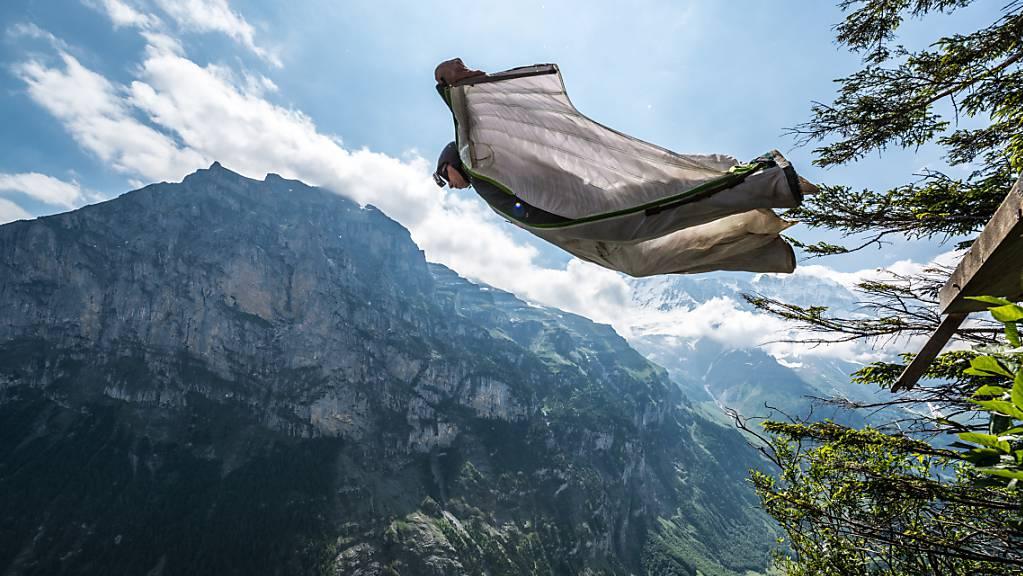 Ein Base-Jumper springt mit seinem Wingsuit in Lauterbrunnen von einem Felsen in die Tiefe. (Archiv)