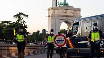 Polizisten stehen an einem Kontrollpunkt in Madrid. Die Justiz hat die umstrittene Zwangsabriegelung des Corona-Hotspots Madrid durch die spanische Zentralregierung gekippt. Foto: Diego Radames/SOPA Images via ZUMA Wire/dpa