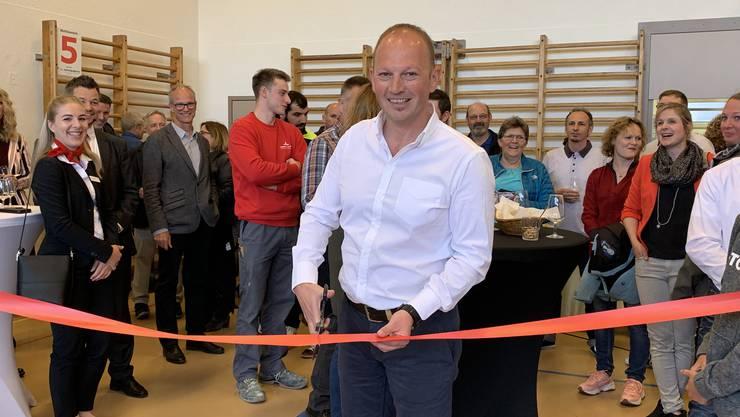 Ein gut gelaunter OK-Präsident Heinz Lüem schneidet das rote Band durch und eröffnet die Ausstellung.