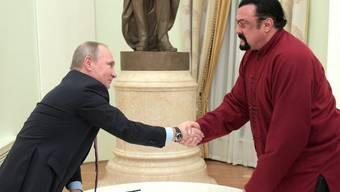 Action-Schauspieler Steven Seagal (r) darf die Ukraine in den nächsten fünf Jahren nicht mehr besuchen. Er gilt als Freund des russischen Präsidenten Putin (l). (Archiv)