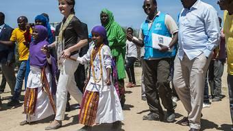 Die Schweizer Bundespräsidentin Simonetta Sommaruga mit zwei Flüchtlingskindern an der Hand im Sheder Flüchtlingslager