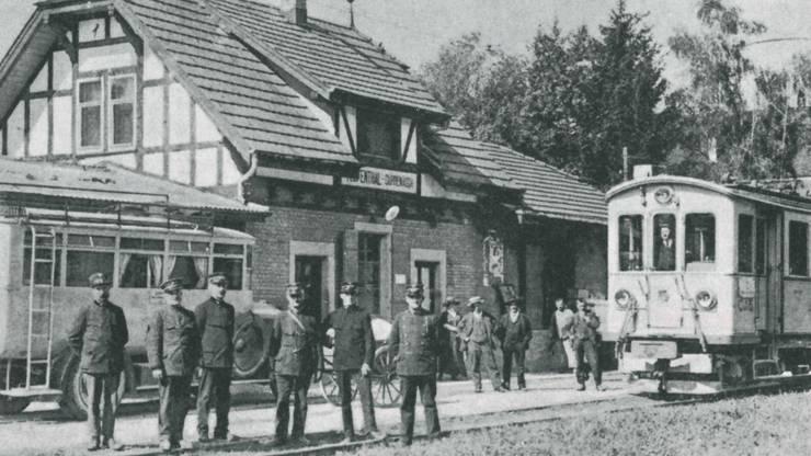 Postbeamte mit Postauto und Zug beim Bahnhof Teufenthal-Dürrenäsch (undatierte Aufnahme).